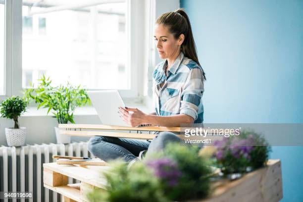 Beautiful woman refurbishing her home with pallets, using laptop
