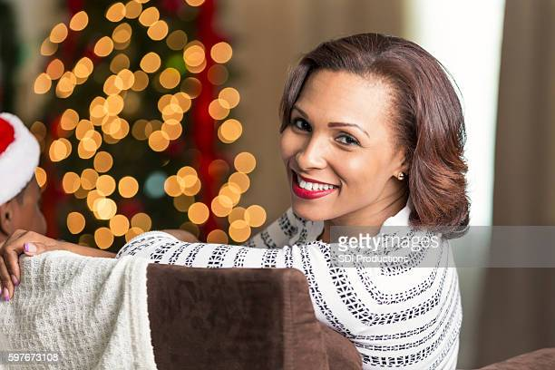 beautiful woman relaxes with family at christmastime - mid adult woman sweater stock pictures, royalty-free photos & images