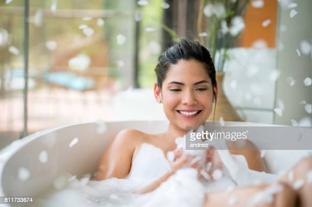 beautiful woman relaxing at home with a bubble bath - taking a bath stock pictures, royalty-free photos & images