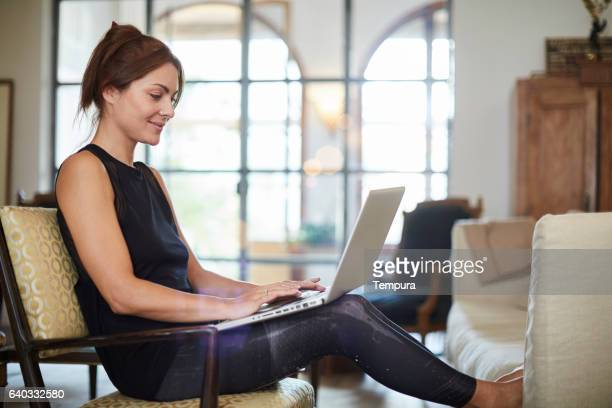 beautiful woman relaxing at home with laptop. - yoga pants stock photos and pictures