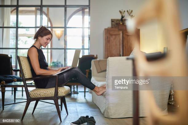 Beautiful woman relaxing at home with laptop.