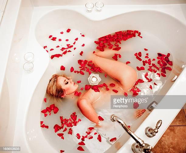 Belle femme de détente dans un luxueux bain au lait de Rose