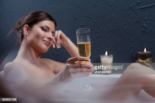 Beautiful woman relaxing in bathtub holding a glass of champagne