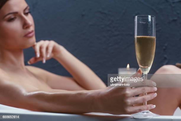 Beautiful woman relaxing in bathtub with lighted candles. 29 years woman taking a bath and drinking champagne. Steamy.New Age Beauty & Wellness