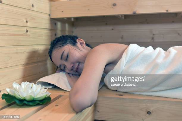 Beautiful woman relaxing in sauna and staying healthy .