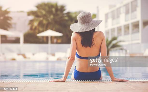 beautiful woman relaxing in swimming pool with sun hat - istock photo stock pictures, royalty-free photos & images