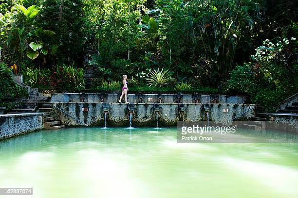 A beautiful woman relaxing next to a hot springs surrounded by a lush jungle and flowers in Bali, Indonesia.