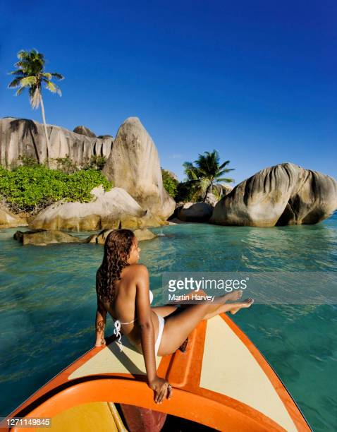 beautiful woman relaxing on boat on a tropical island paradise. anse source d' argent beach la digue island seychelles. - indian ocean stock pictures, royalty-free photos & images