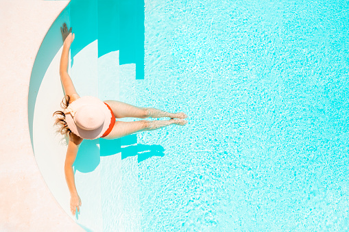Beautiful woman relaxing on pool steps. High angle view. - gettyimageskorea
