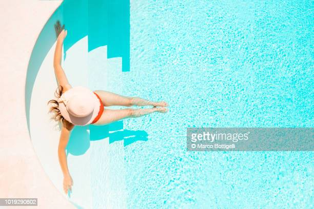 Beautiful woman relaxing on pool steps. High angle view.