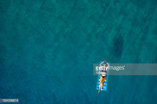 beautiful woman relaxing on turquoise sea with sea bed