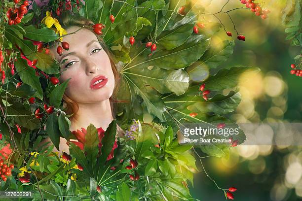 beautiful woman resting her head against plants