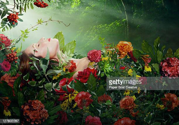 beautiful woman resting on a bed of red roses