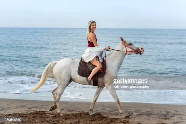 美しい女性はビーチで馬に乗ります - アフィントンの白馬 ストックフォトと画像