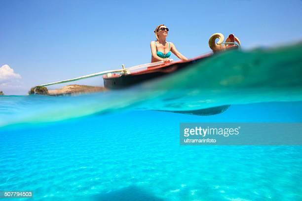 Beautiful woman rowing fishing boat