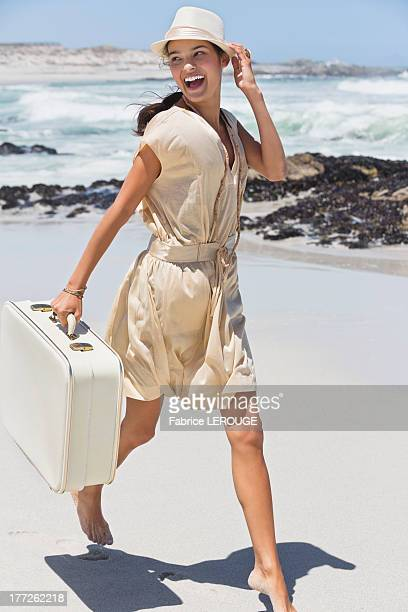 Beautiful woman running with a suitcase on the beach