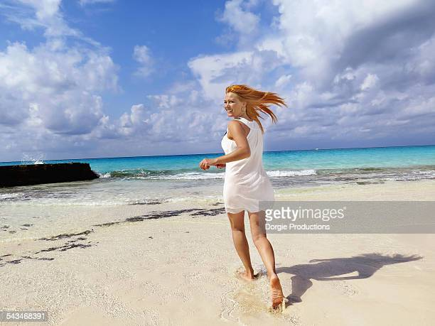 Beautiful woman runs joyfully on a tropical beac