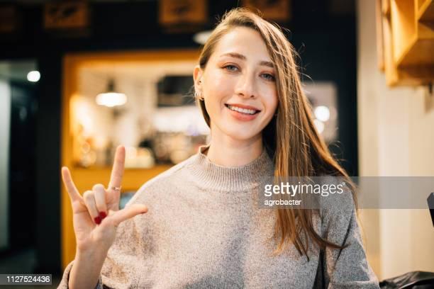 mooie vrouw zeggen ik hou van jou in gebarentaal - gebaren stockfoto's en -beelden