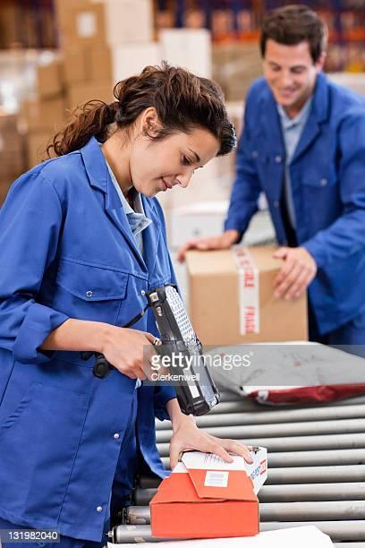 Beautiful woman scanning barcodes on conveyor belt