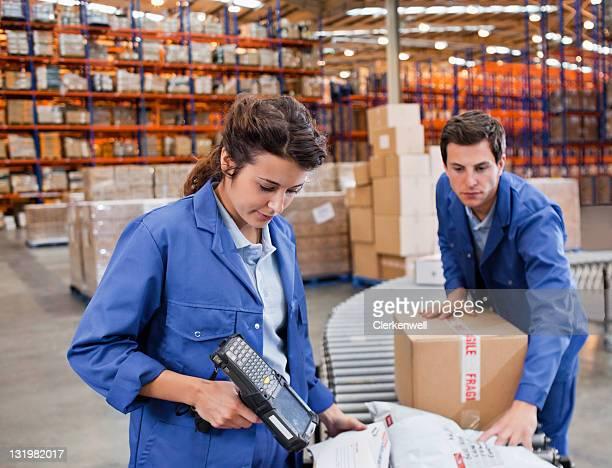 Schöne Frau Scannen Sie die Strichcodes mit männliche Arbeitnehmer Schieben cardb