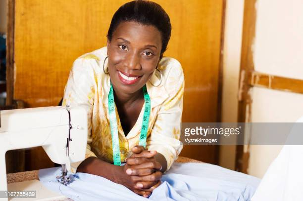 beautiful woman seamstress smiling leaning on the table of her sewing machine and looking at the camera - femme ivoirienne photos et images de collection