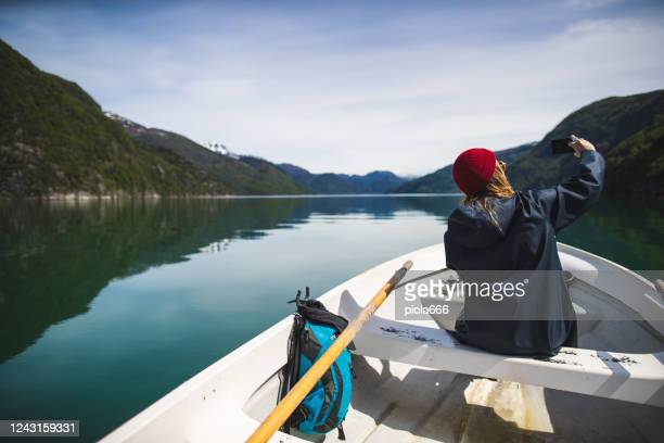 beautiful woman selfie with mobile phone on a small fishing boat: sailing in a fjord in norway - vintage raincoat stock pictures, royalty-free photos & images