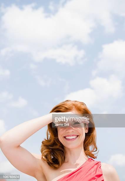 Beautiful woman shielding her eyes from the sun