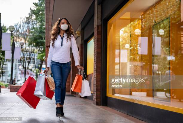 beautiful woman shopping at the mall wearing a facemask - biosecurity stock pictures, royalty-free photos & images