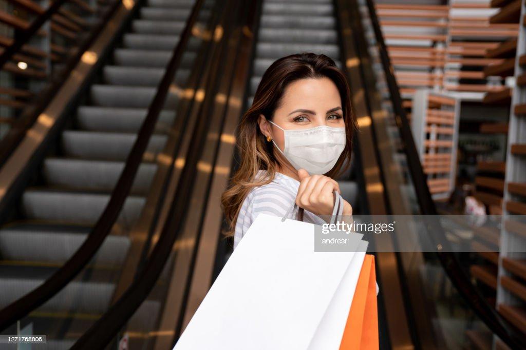 Mooie vrouw die bij het wandelgalerij het dragen van een facemask draagt : Stockfoto