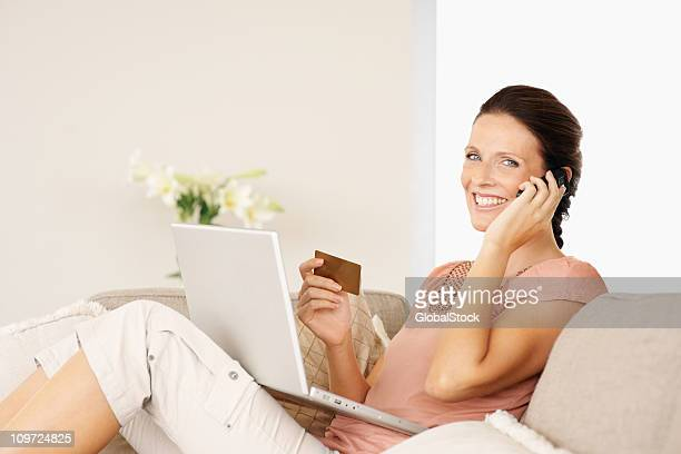 beautiful woman shopping online with a mobile phone and laptop - one mid adult woman only stock pictures, royalty-free photos & images