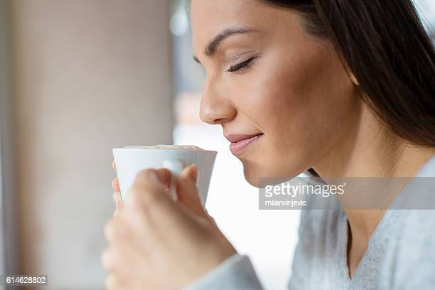 beautiful woman sipping her coffee - cappuccino - fotografias e filmes do acervo