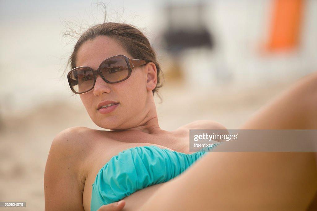 Beautiful woman sit on the sand : Stock Photo