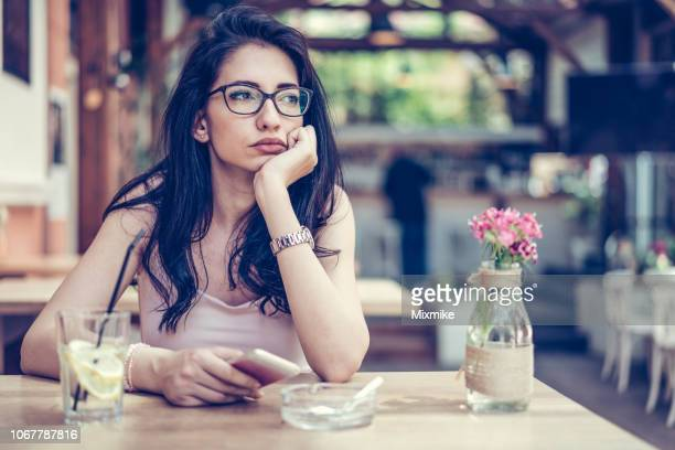 beautiful woman sitting alone at the café - unhealthy living stock pictures, royalty-free photos & images