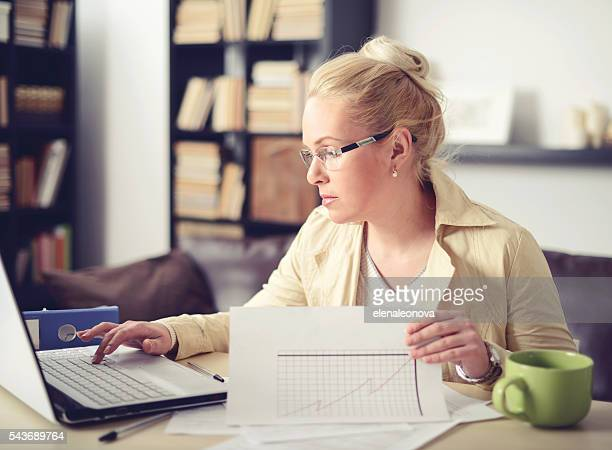 beautiful woman sitting at the table and working at home