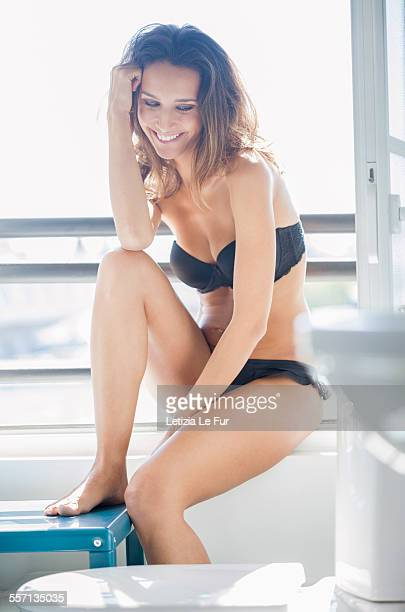 beautiful woman sitting in bathroom and smiling - lingerie stock pictures, royalty-free photos & images