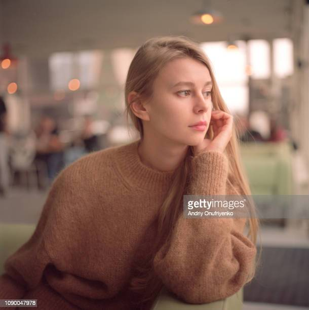 beautiful woman sitting in cafe - three quarter length stock pictures, royalty-free photos & images