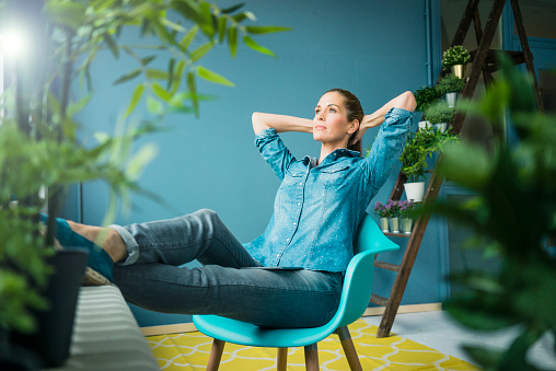 Beautiful woman sitting in her home, decorated with plants, daydreaming - gettyimageskorea