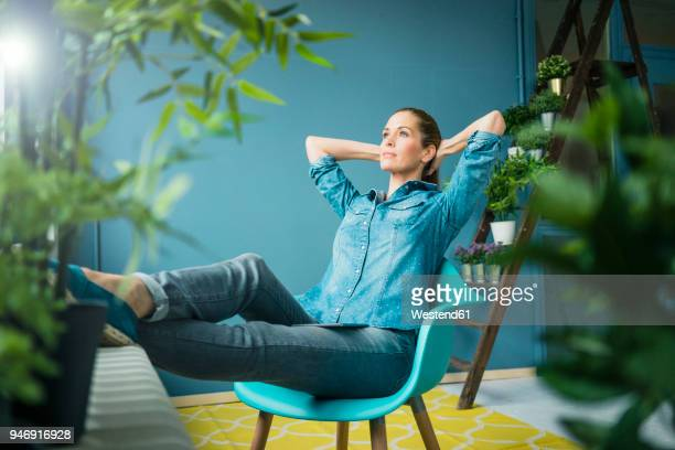 Beautiful woman sitting in her home, decorated with plants, daydreaming