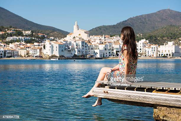beautiful woman sitting on a dock in cadaqués - cadaques stock pictures, royalty-free photos & images