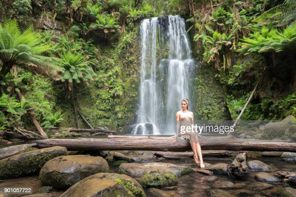 beautiful woman sitting on a log in front a stunning waterfall, back to nature, beauchamp falls, great ocean road - falling water stock photos and pictures