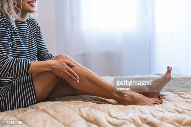 beautiful woman sitting on bed and applying cream on legs - essential oil stock pictures, royalty-free photos & images