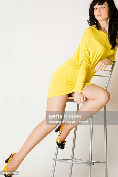 Beautiful Woman Sitting On Chair Against White Background