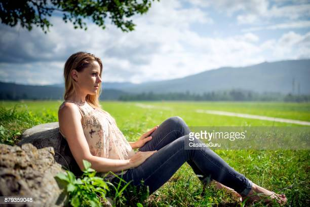 Beautiful Woman Sitting on Grass in the Countryside