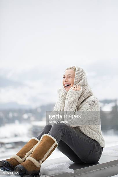 beautiful woman sitting on ledge of wall and smiling, crans-montana, swiss alps, switzerland - stiefel stock-fotos und bilder