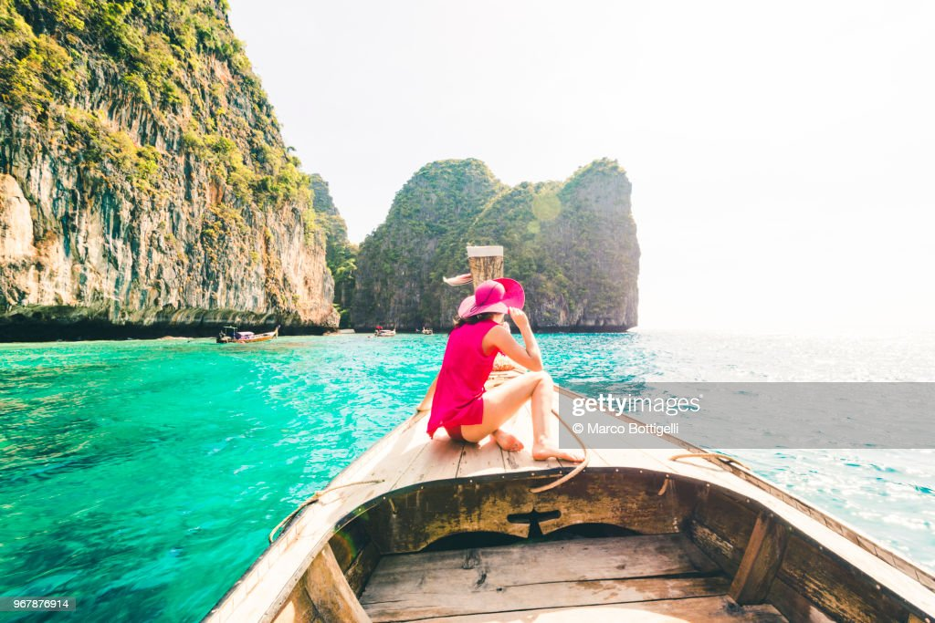 Beautiful woman sitting on longtail boat at Phi Phi Islands. : Stock Photo