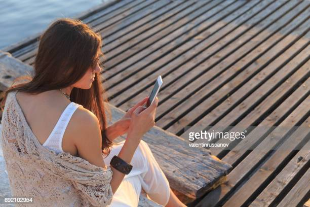 beautiful woman sitting on wooden pier and using smart phone - off shoulder stock pictures, royalty-free photos & images