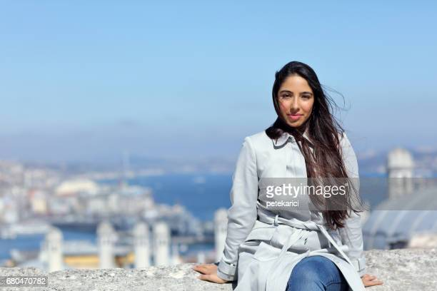 Beautiful woman sitting out the Suleymaniye Mosque enjoying the amazing view of Istanbul, Turkey