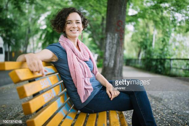 beautiful woman sitting outside on bench - park bench stock pictures, royalty-free photos & images