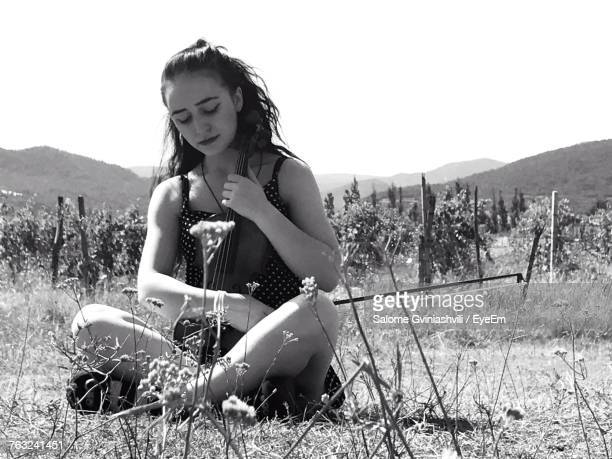 Beautiful Woman Sitting With Violin On Sunny Day