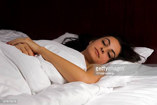 Beautiful woman sleeping in soft bed and fluffy quilt